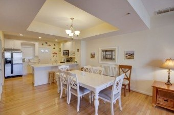 condo with full kitchen with white cabinets dining table and chairs